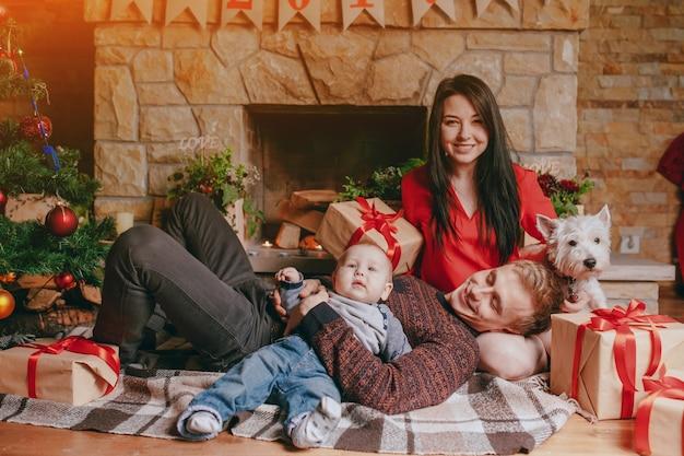Moeder zit op de vloer, terwijl de vader rust zijn hoofd op haar schoot en houdt de baby met een arm