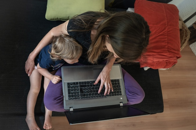 Moeder zittend op de bank met laptopcomputer werken met haar peuter dochter knuffelen naast haar.