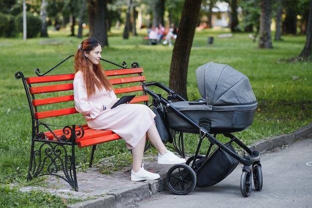 Moeder zittend op een bankje. vrouw duwt haar peuter zittend in een kinderwagen. dame met een tablet.