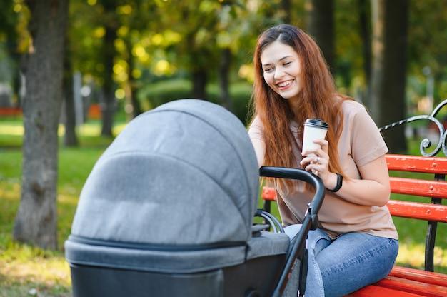 Moeder zittend op een bankje. vrouw duwt haar peuter zittend in een kinderwagen. familieconcept.
