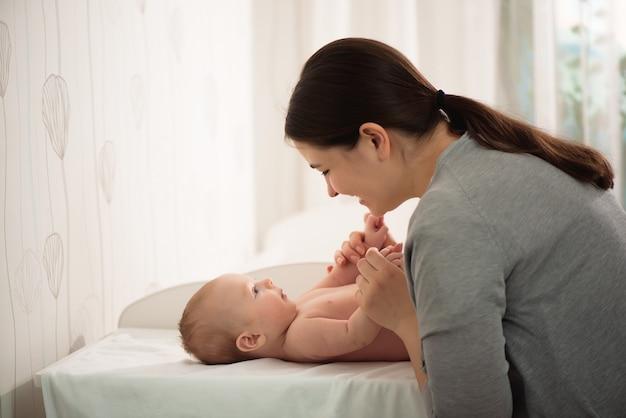 Moeder zogende baby. vrouw en pasgeboren jongen ontspannen in een witte slaapkamer.