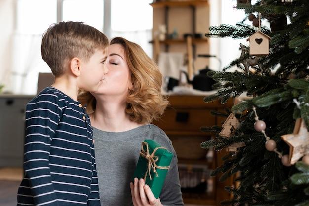 Moeder zoon kussen op de wang op eerste kerstdag