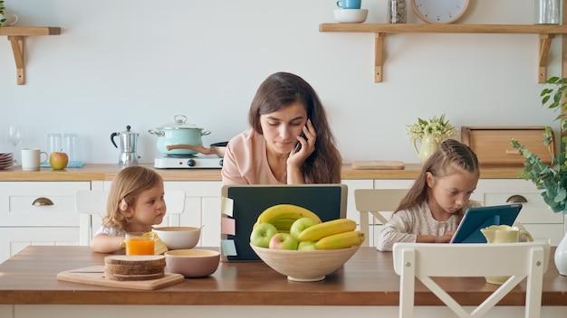 Moeder zorgt voor haar dochters terwijl ze met een laptop aan tafel werkt en een zakelijk gesprek voert aan de telefoon in de keuken. moeder werkt op afstand, terwijl haar gezin zichzelf isoleert.