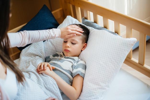 Moeder zorgt voor haar kind dat koorts heeft. ziekte en gezondheidszorg
