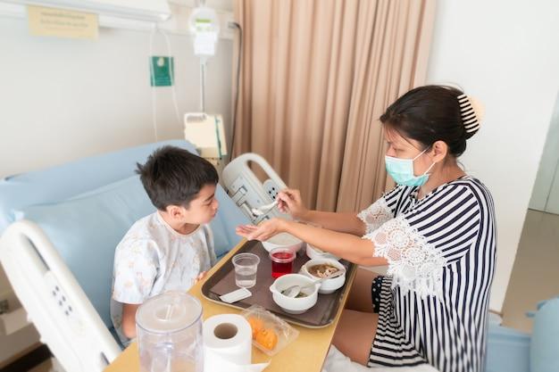 Moeder zorgt voor haar zoon terwijl hij in het ziekenhuis zint