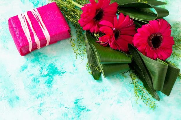 Moederdag achtergrond of wenskaart boeket rode bloemen van gerbera en een cadeautje kopieer de ruimte