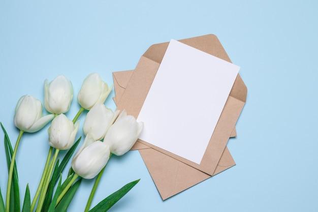 Moederdag. bovenaanzicht van tulpen en ambachtelijke envelop met een vlakke brief,
