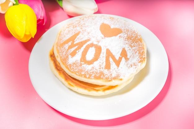 Moederdag brunch restaurant uitnodiging concept. verschillende moms womans day menu-achtergrond, met traditioneel ontbijt en lunch eten en drinken, met bloemen op zonnige roze achtergrond
