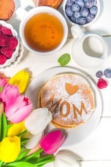 Moederdag brunch restaurant uitnodiging concept. verschillende moms womans day menu-achtergrond, met traditioneel ontbijt en lunch eten en drinken, met bloemen op zonnige witte houten achtergrond