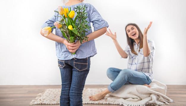 Moederdag, een dochtertje geeft haar moeder een boeket tulpen.