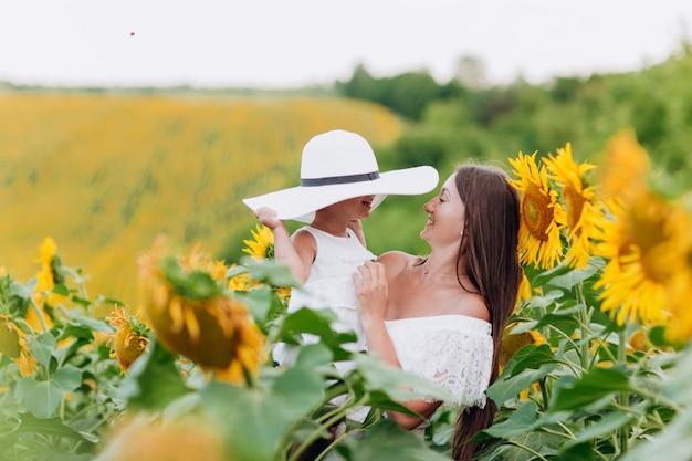 Moederdag. gelukkige moeder met de dochter in het veld met zonnebloemen. moeder en babymeisje plezier buitenshuis. familie concept.