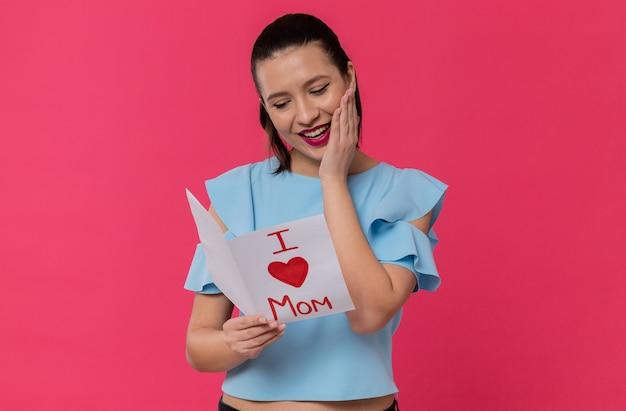 Moederdag. glimlachende mooie jonge vrouw die brief van haar kind leest: ik hou van mama