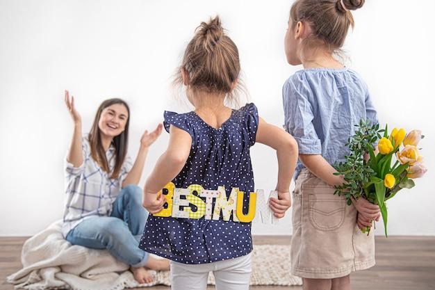 Moederdag. groeten en cadeaus van kinderen. twee kleine schattige meisjes feliciteren hun moeder met een boeket verse lentetulpen en een inscriptie. familiewaarden en vakanties.