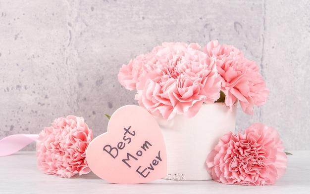Moederdag handgemaakte geschenkdoos verrassing wensen fotografie - mooie bloeiende anjers met roze lint doos geïsoleerd op grijs behang ontwerp, close-up, kopieer ruimte