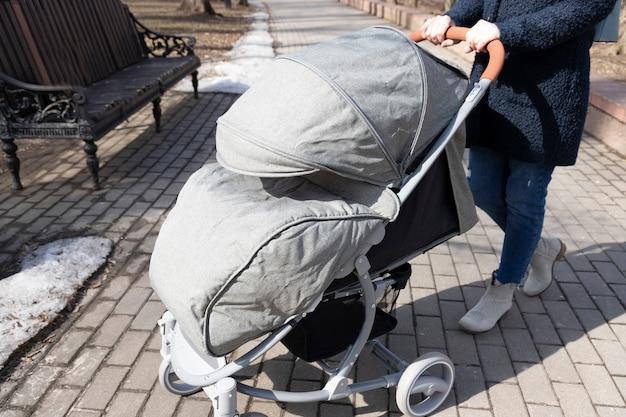 Moederdag. jonge vrouw die in de lentepark met kinderwagen loopt. moeder brengt buiten tijd door met haar kind