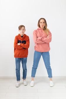 Moederdag, kinderen en familie concept - tienerjongen en zijn moeder die zich voordeed op witte muur.