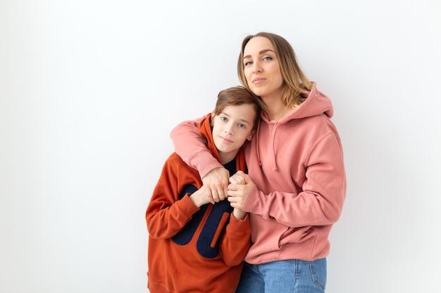 Moederdag, kinderen en familie concept - tienerjongen knuffelen zijn moeder op wit