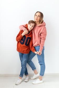 Moederdag, kinderen en familie concept - tienerjongen knuffelen zijn moeder op witte muur