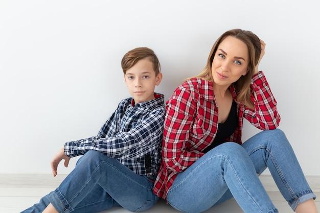 Moederdag, kinderen en familieconcept - leuke tienerjongen met zijn jonge moeder thuis