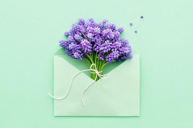 Moederdag. lila lentebloemen in turquoise envelop.