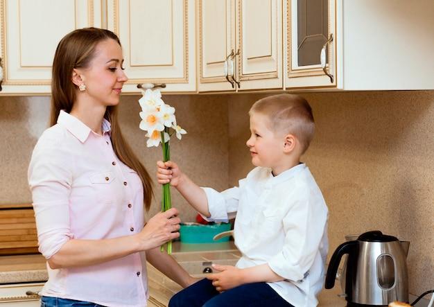 Moederdag, vakantie en familieconcept - gelukkig zoontje geeft thuis bloemen aan zijn lachende moeder. een kind geeft mama een boeket narcissen
