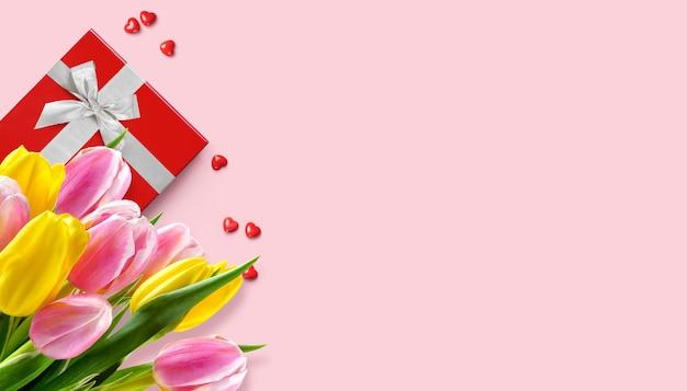 Moederdag valentijn wenskaart met tulpen boeket en rode geschenkdoos op roze achtergrond. ruimte kopiëren
