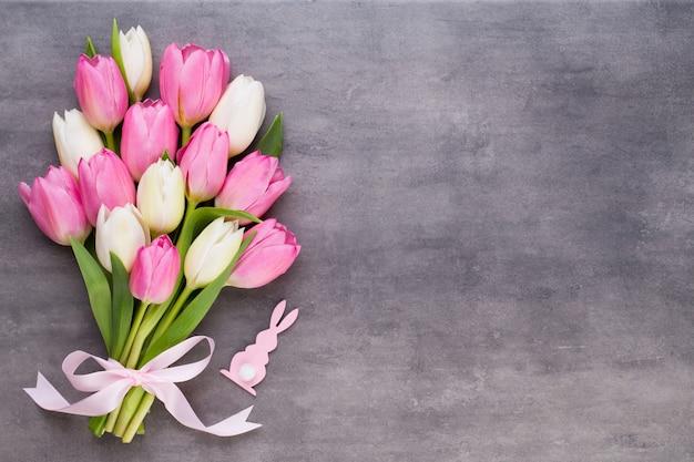 Moederdag, vrouwendag, pasen, roze tulpen, cadeautjes op een grijze ondergrond.