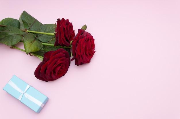 Moederdag wenskaart, drie rode rozen en geschenkdoos. kopieer ruimte