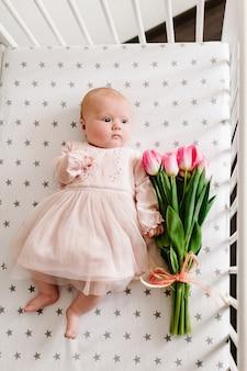 Moederdagbericht met het pasgeboren babymeisje dat de bloem vasthoudt en op een bed ligt met een boeket roze tulpen.