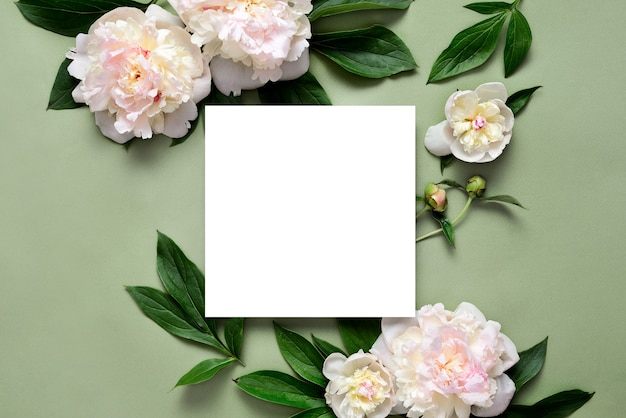 Moederdagkaart of huwelijksuitnodigingskaart met bloeiende pioenrozen die op groen oppervlak liggen, lege ruimte voor een tekst