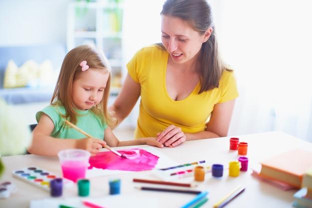 Moederdochter schildert waterverf op een vel papier om thuis te zitten aan de tafel in een lichte kamer.