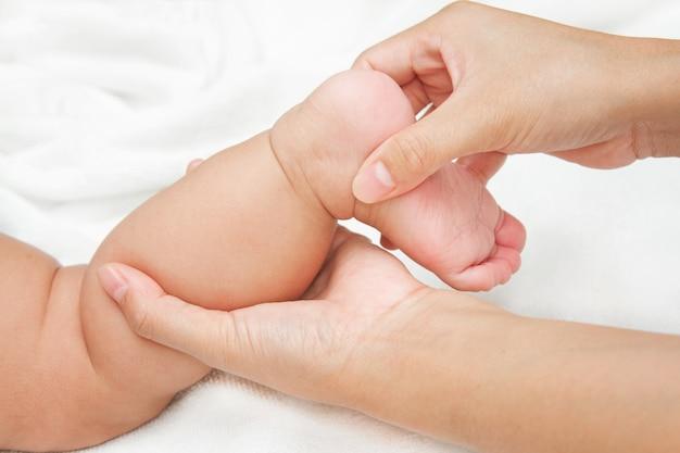 Moederhand die been en voet van haar baby masseert
