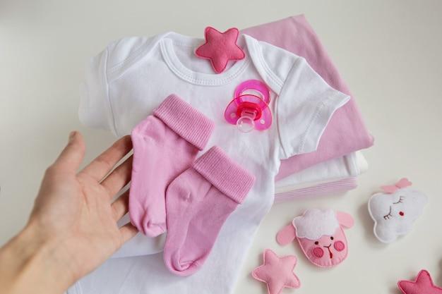 Moederhand houdt de roze sokken van de toekomstige dochter van het kind vast