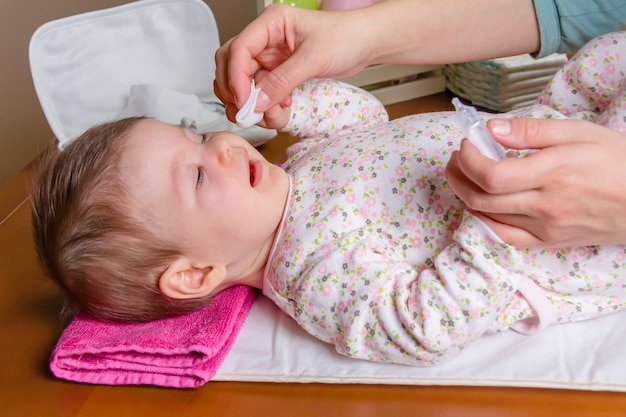 Moederhanden die de ogen van de baby schoonmaken met fysiologisch serum in een wattenschijfje