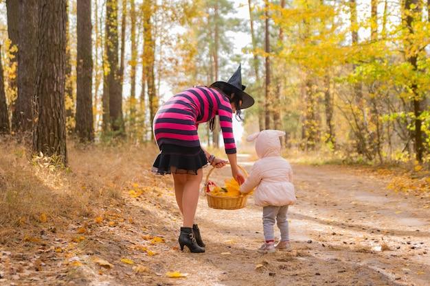 Moederheks die babykonijn helpt om op halloween-kostuumfeest voor herfstparkviering te lopen