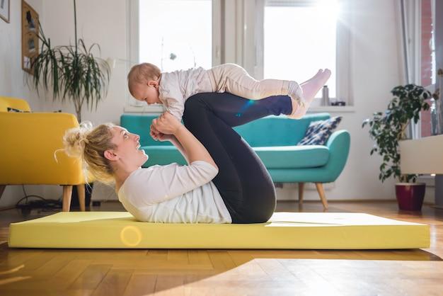 Moederoefening met haar baby thuis