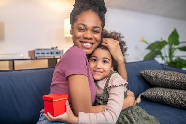 Moeders geluk. glanzende, donkere, schattige moeder omhelsde een glimlachende kleine dochter met een kleine rode doos die op de bank zat