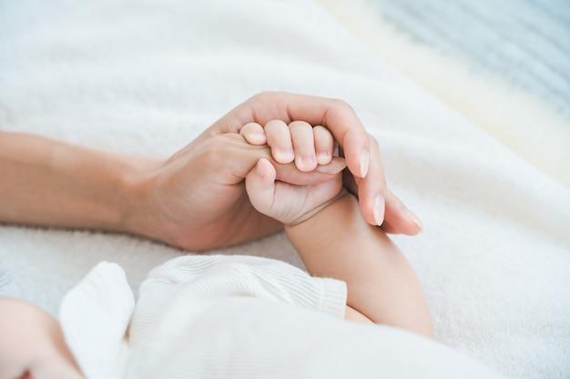 Moeders hand ondersteunt de hand van haar baby