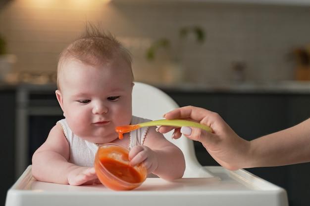 Moeders hand voedt een lepel met het eerste aas van een zes maanden oude baby