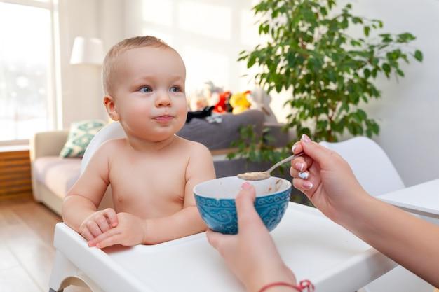 Moeders hand voedt grappige schattige gelukkige blonde baby peuter met lepel