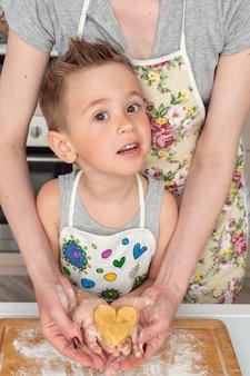 Moeders handen die childshanden met hart gevormd gebakje houden