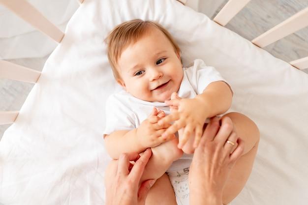 Moeders handen houden de benen van de baby op zijn rug in zijn wieg in een lichte kamer
