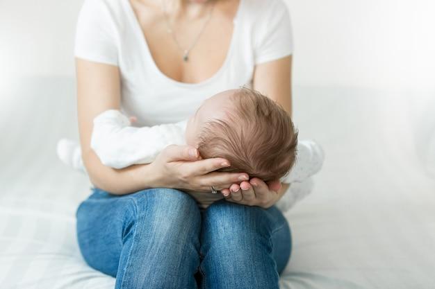 Moeders handen met hoofd van slapende 3 maanden oude babyjongen