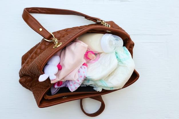 Moeders handtas met items om voor het kind te zorgen.