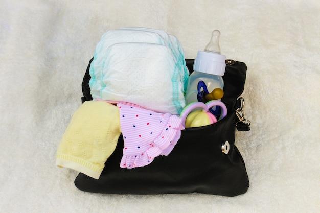 Moeders handtas met items om voor kind te zorgen op wit. bovenaanzicht.