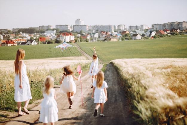 Moeders met dochters spelen in een herfst veld