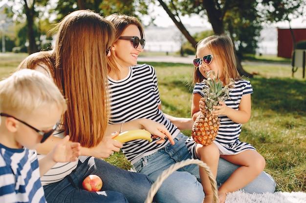 Moeders met kinderen die in een de zomerpark spelen