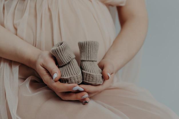 Moederschap en zwangerschap concept. aanstaande moeder bereidt zich voor op de bevalling van kind houdt laarzen in handen poseert binnenshuis in derde trimester