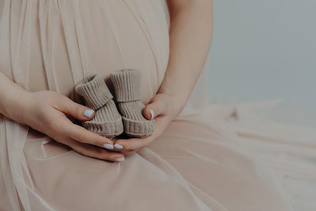 Moederschap en zwangerschap concept. onherkenbare zwangere vrouw houdt kleine laarzen over buik draagt feestelijke jurk. gezichtsloze toekomstige moeder
