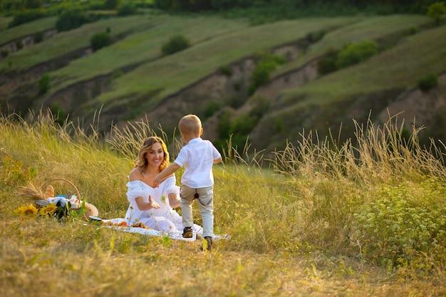 Moederschap. moeder en baby samen hand in hand. moeder en zoon lopen bij de hand in het veld. moederdag. prachtige natuur met mensen. loop samen bij de hand